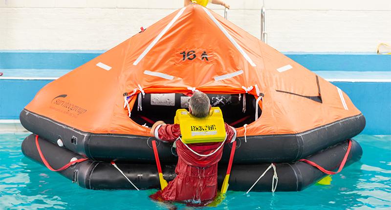 Trainee in pool climbing into life raft
